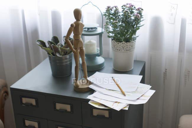Mannequin en bois artiste sur classeur, avec papier et crayon — Photo de stock