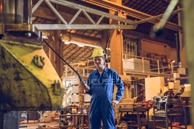 Factory worker wearing protective clothing, holding control lead of manufacturing machine — Stock Photo