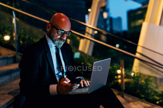 Mature businessman sitting on steps with laptop and smartphone — Stock Photo