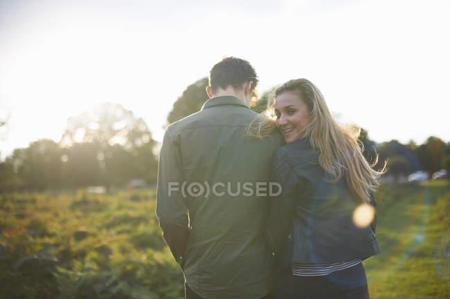 Вид сзади на молодую пару, прогуливающуюся рука об руку в поле — стоковое фото