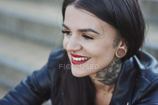 Portrait of young woman smiling, tattoos on neck, nose and ear piercings, close-up — Stock Photo