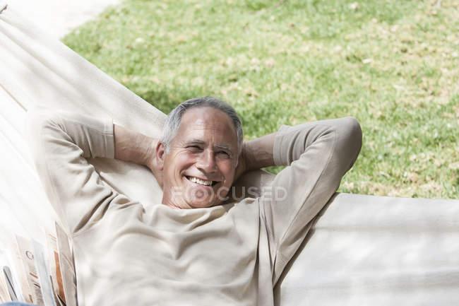 Homem de rede, mãos atrás da cabeça a olhar para a câmara a sorrir — Fotografia de Stock