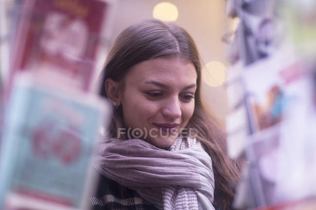 Mujer joven envuelto en la bufanda en compras - foto de stock