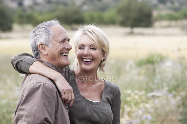 Couple dans le champ souriant — Photo de stock
