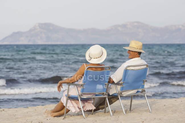 Couple on deckchairs on beach, Palma de Mallorca, Spain — Stock Photo