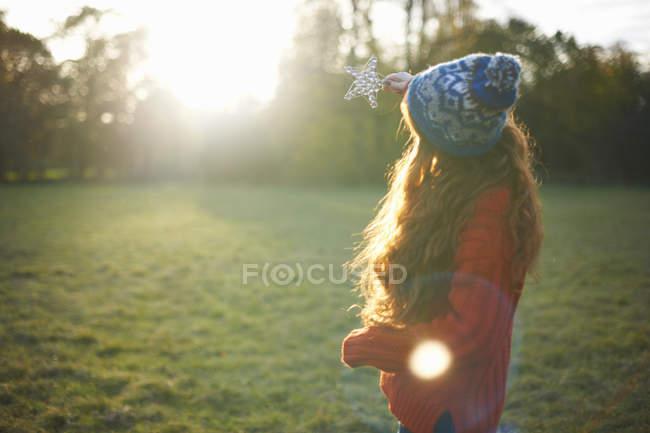 Молодая женщина, держащая звезды вверх к солнечному свету — стоковое фото