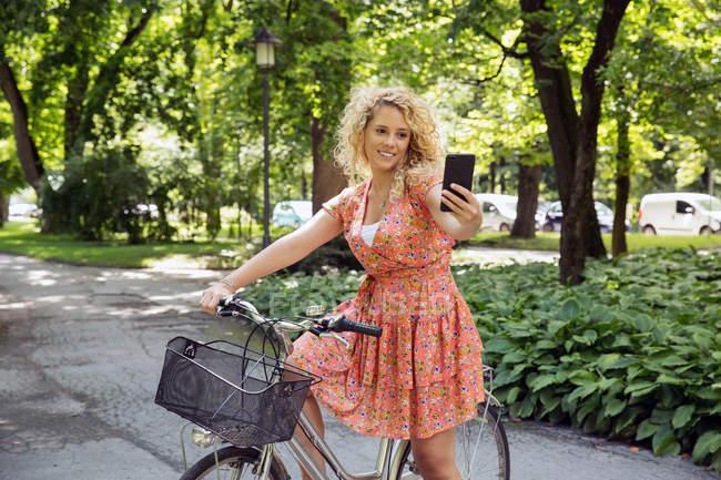 Mujer en bicicleta tomando selfie - foto de stock