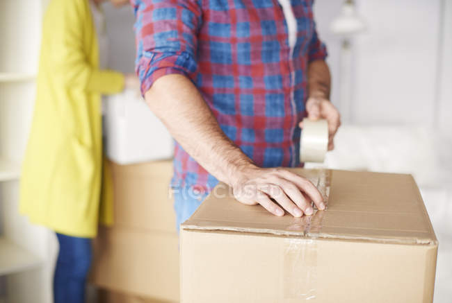 Young couple moving home, young man taping up cardboard box, mid section — Stock Photo
