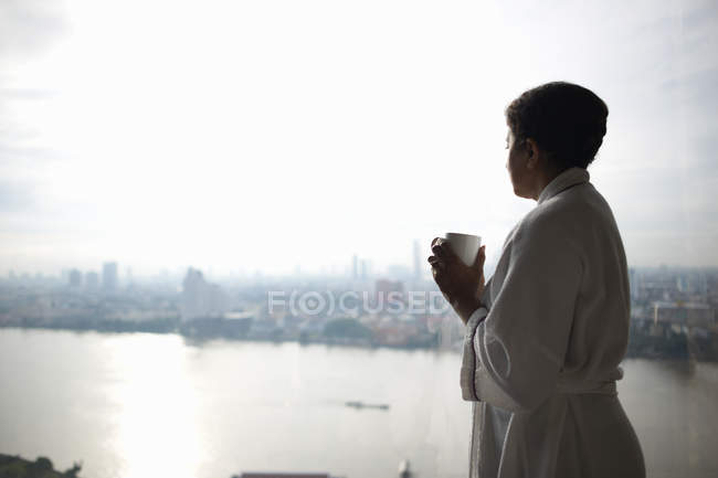 Woman holding cup and looking at view of city, Bangkok, Krung Thep, Thailand, Asia — Stock Photo