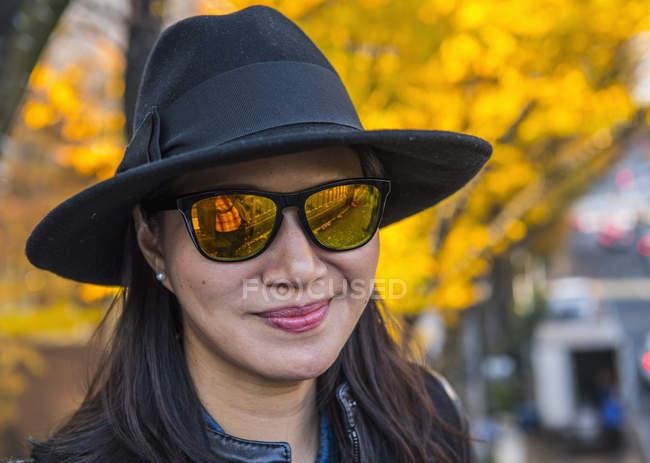 Portrait de femme asiatique avec des lunettes de soleil jaunes au jardin National Shinjuku Gyoen, Tokyo — Photo de stock
