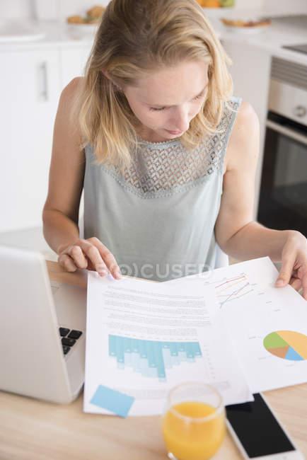Молода жінка з ноутбуком, дивлячись на оформлення документів на кухонному столі — стокове фото