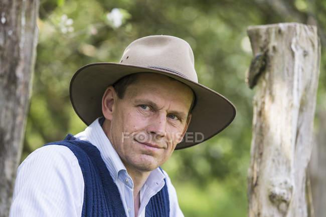 Retrato de homem de chapéu perto do portão de madeira — Fotografia de Stock