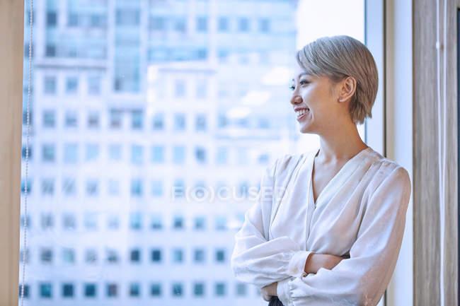 Retrato de una joven empresaria sonriendo cerca de la ventana - foto de stock