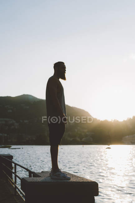 Young male looking out from waterfront, Lake Como, Lombardy, Italy — Stock Photo