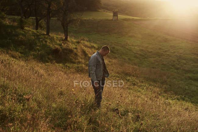 Homem adulto médio em pé na encosta ao pôr do sol — Fotografia de Stock