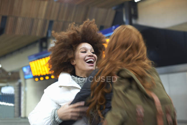 Two young women greeting each other at train station — Stock Photo