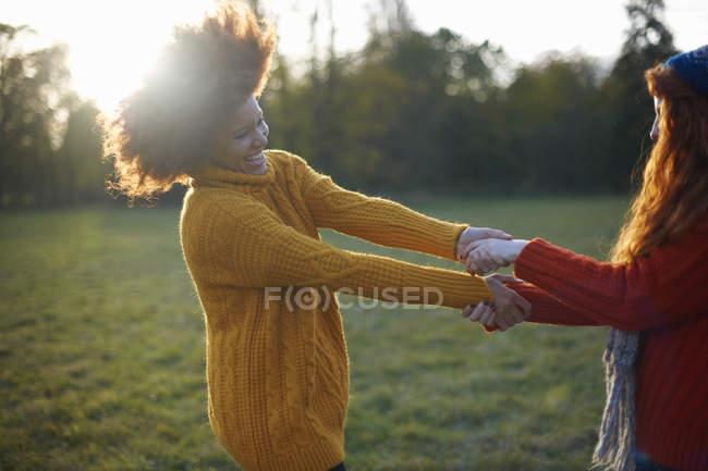 Due giovani donne che tengono le mani e scherzare — Foto stock