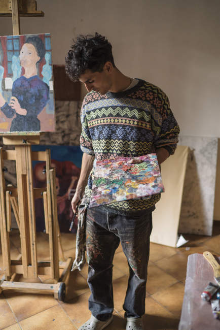 Young artist holding palette in artist studio — Stock Photo