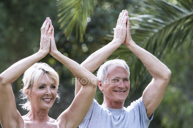 Couple, hands together, arms raised in yoga position — Stock Photo