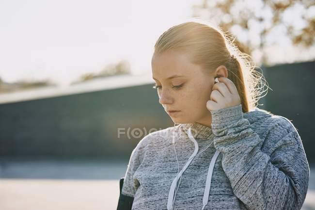 Mujer joven entrenando e insertando auriculares - foto de stock
