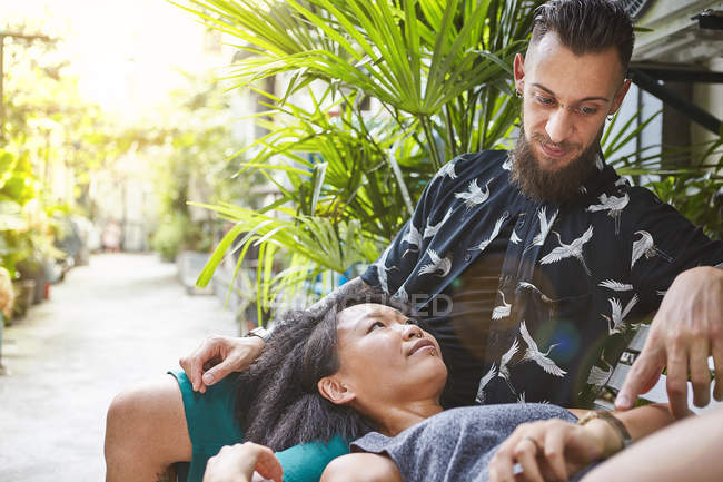 Multi ethnic couple reclining on garden bench in residential alleyway, Shanghai French Concession, Shanghai, China — Stock Photo