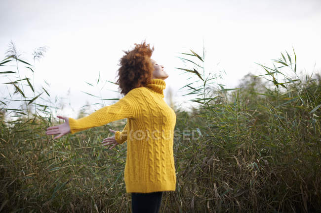 Side view of woman with open arms in rural setting — Stock Photo