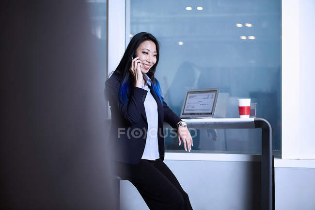 Businesswoman making telephone call and smiling — Stock Photo