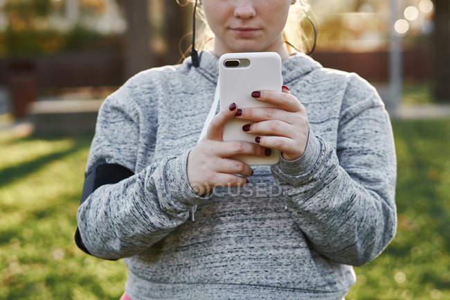 Молодая женщина тренируется в парке и смотрит на смартфон — стоковое фото