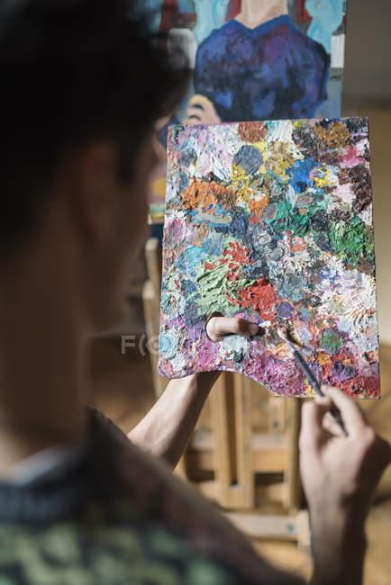 En vista del hombro del hombre artista mezcla pinturas al óleo en la paleta de - foto de stock