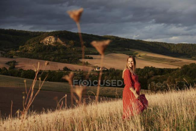 Retrato de mulher grávida feliz em vestido vermelho na encosta — Fotografia de Stock
