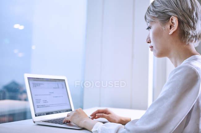Vista laterale della donna d'affari utilizzando il computer portatile — Foto stock