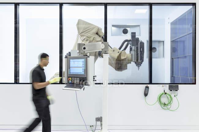 Roboteringenieur bedient Roboter-Schneidmaschine in Robotik-Forschungseinrichtung — Stockfoto