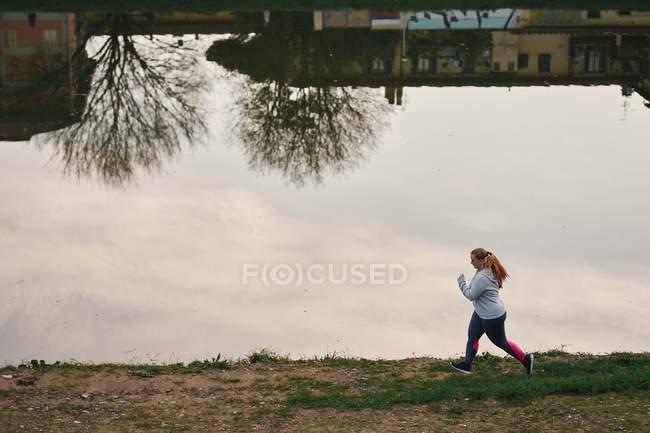 Jeune femelle courbée courant au bord de la rivière — Photo de stock