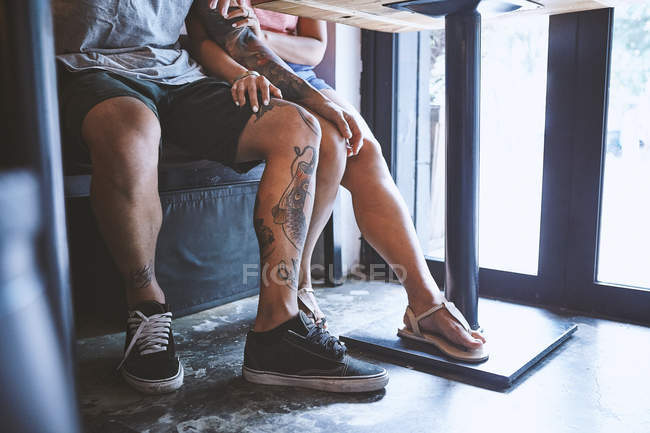 Waist down of multi ethnic hipster couple in cafe with hand on each others knee, Shanghai French Concession, Shanghai, China — Stock Photo