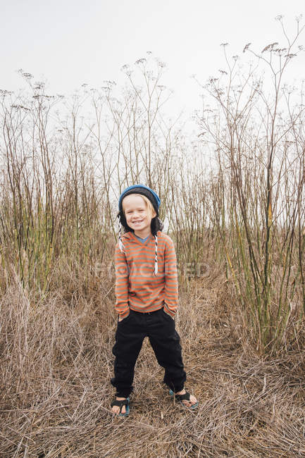 Portrait of boy with hands in pockets in rural setting — Stock Photo