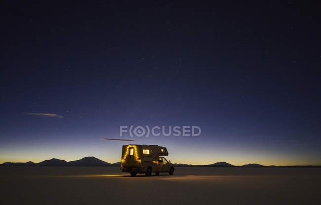 Recreational vehicle, travelling at dusk, across salt flats, Salar de Uyuni, Uyuni, Oruro, Bolivia, South America — Fotografia de Stock