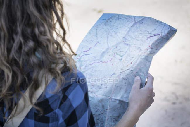 Обрезанное мнение женщины, глядя на складной карте — стоковое фото