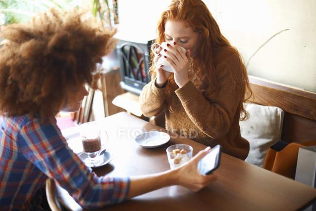 Due amici con smartphone si rilassano nel caffè — Foto stock