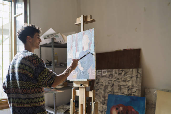 Male artist painting at easel in artist studio — Stock Photo