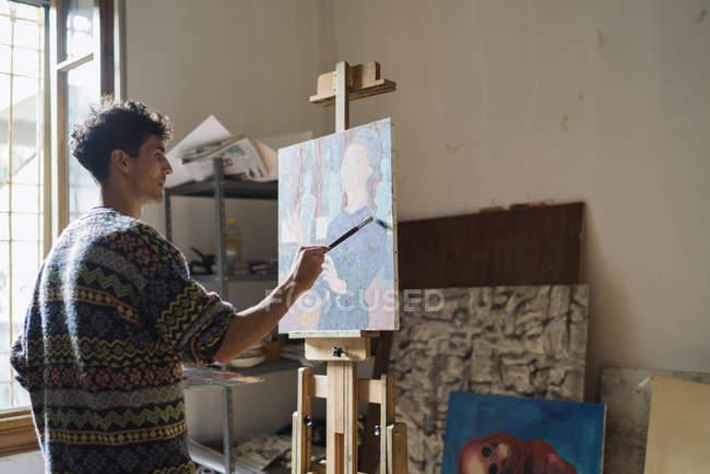Чоловічий художник живопис на мольберті у художньої студії — стокове фото