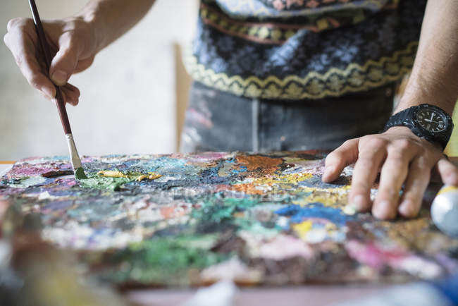 Artist mixing oil paints on palette in studio — Stock Photo