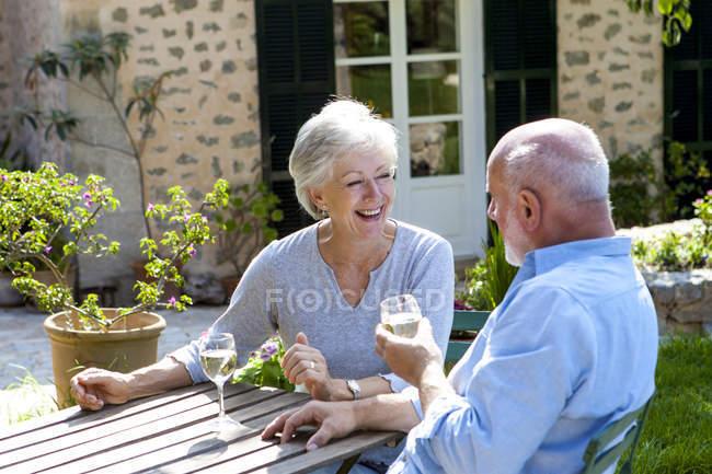 Senior couple sitting in garden, enjoying glass of wine — Stock Photo