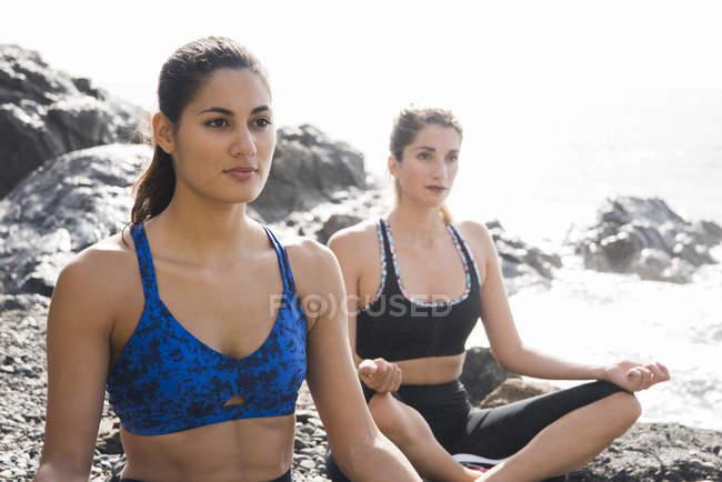 Dos jóvenes practicando yoga en la playa - foto de stock