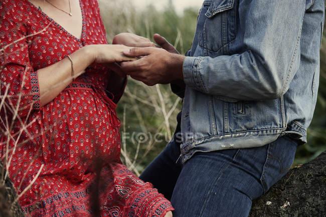 Середина романтической беременной пары, держащейся за руки — стоковое фото