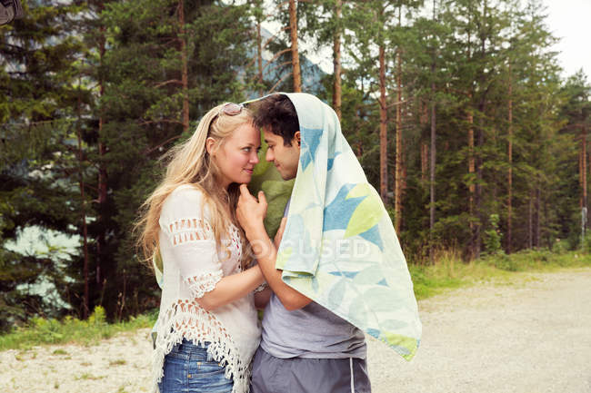 Couple wrapped in towel, face to face hugging — Stock Photo
