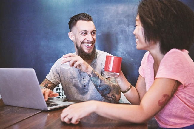 Multi ethnic hipster couple in cafe using laptop, Shanghai French Concession, Shanghai, China — Stock Photo