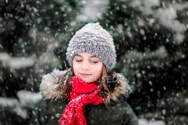 Ritratto di ragazza con gli occhi chiusi nella neve che cade — Foto stock