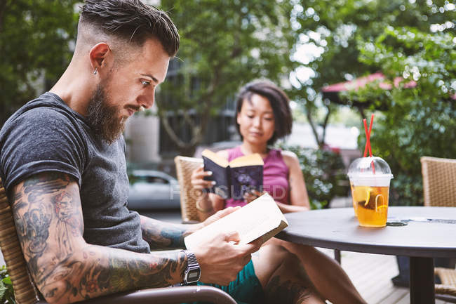 Multi ethnic hipster couple reading books at sidewalk cafe, Shanghai French Concession, Shanghai, China — Stock Photo