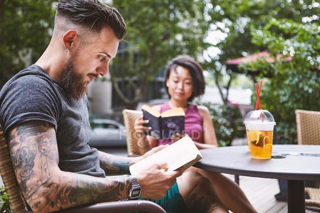 Multi ethnic hipster couple reading books at sidewalk cafe, Shanghai French Concession, Shanghai, China — Stock Photo