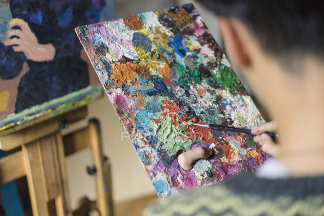 Male artist mixing oil paint on palette in artist studio — Stock Photo